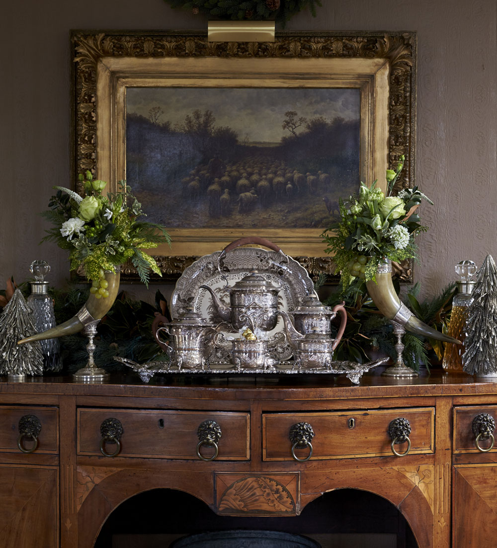a pair of green and white arrangements in antique sterling silver on an antique sideboard