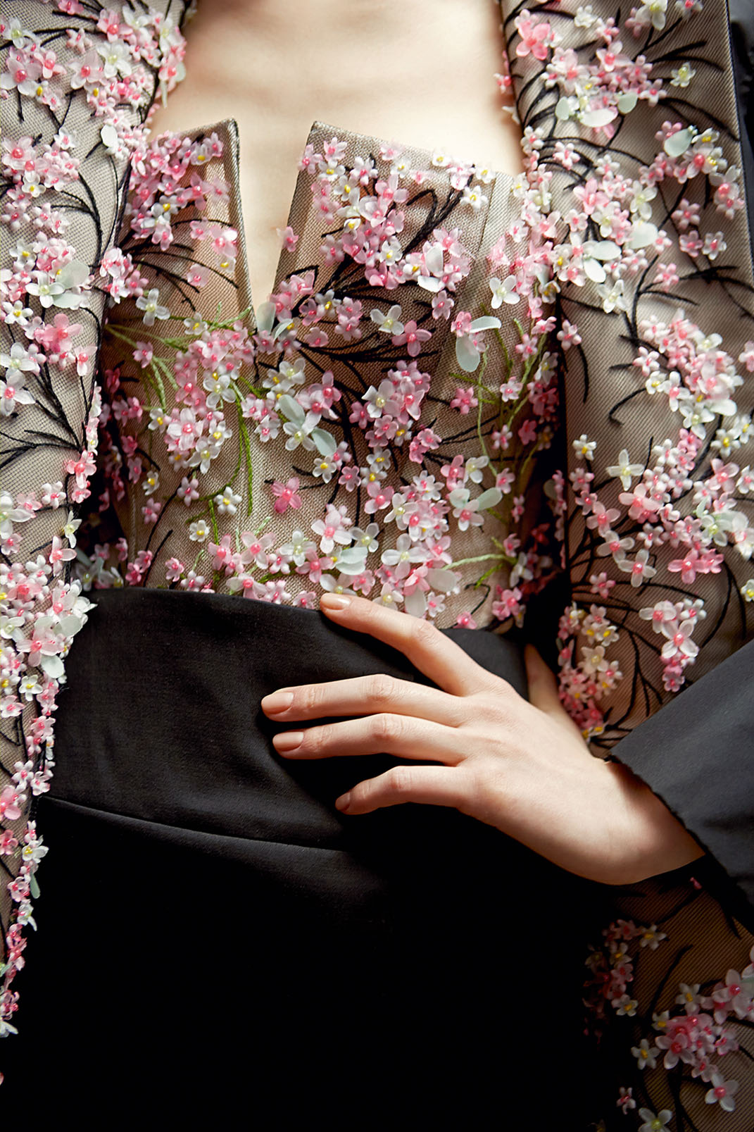 High fashion photo of a model wearing a floral Dior blouse and black skirt