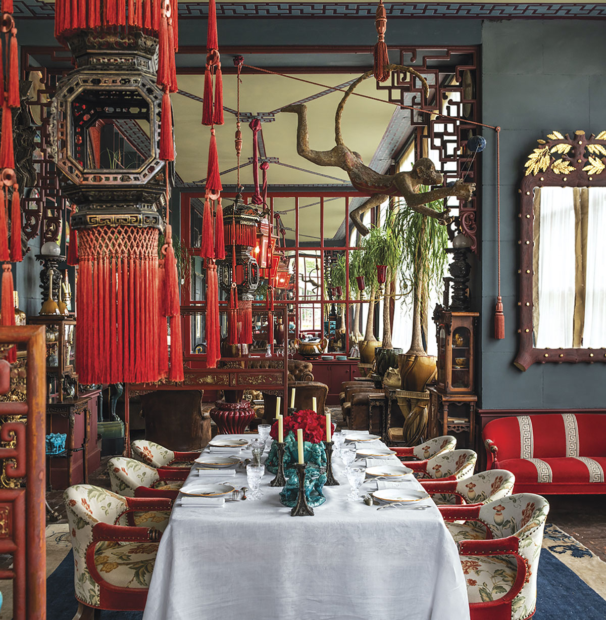 A table for 6 in a Chinese-inspired dining room. The primary color is dusty blue with bright red accents. From the pages of Be My Guest by Pierre Sauvage and Olivia Roland