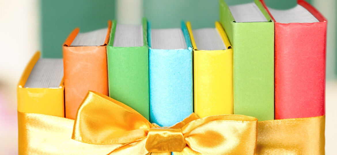 row up books with bright and colorful covers (yellow, orange, green, blue, and red), tied together with a yellow satin bow. Royalty-free stock photo ID: 323036612 Books. By Billion Photos. Shutterstock