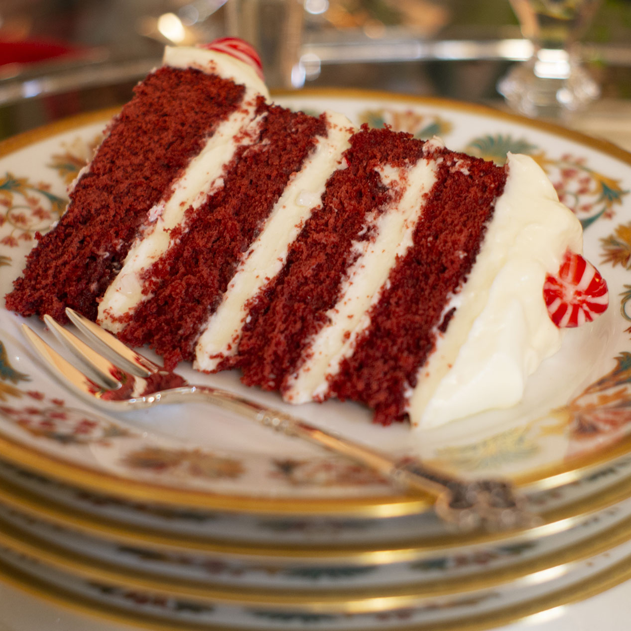 A slice of Peppermint Red Velvet Cake on a Haviland Haute Epoque Dessert Plate with a Christofle Renaissance dessert fork, both from Replacements, Ltd, on a holiday dessert table