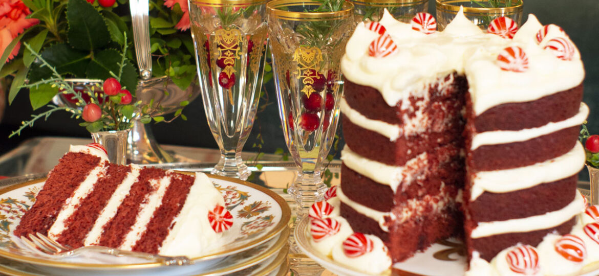 A holiday dessert table featuring a 4-layer red velvet cake on a pedestal and champagne in glasses garnished with rosemary sprigs and cranberries. In the background, an arrangement of red flowers fills a silver basket.