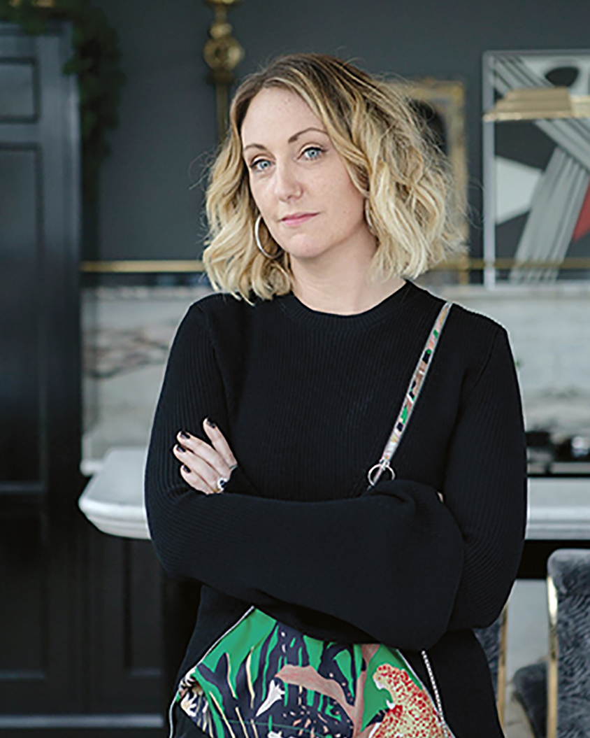 portrait of the Irish artist Eva O'Donovan, wearing black and carrying a colorful, floral fabric shoulder bag