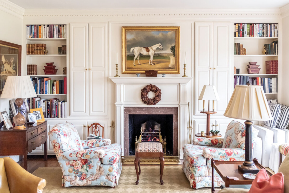 Living room scene with white paneled walls, a white mantel, flanked by built in book shelves and floral upholstered club chairs