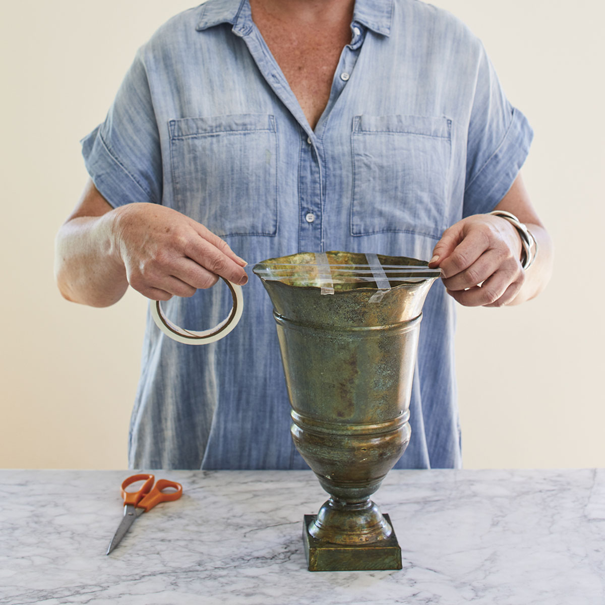 floral designer Kirk Whitfield demonstrates how to make a tape grid on the top of a flower vase (step 1)