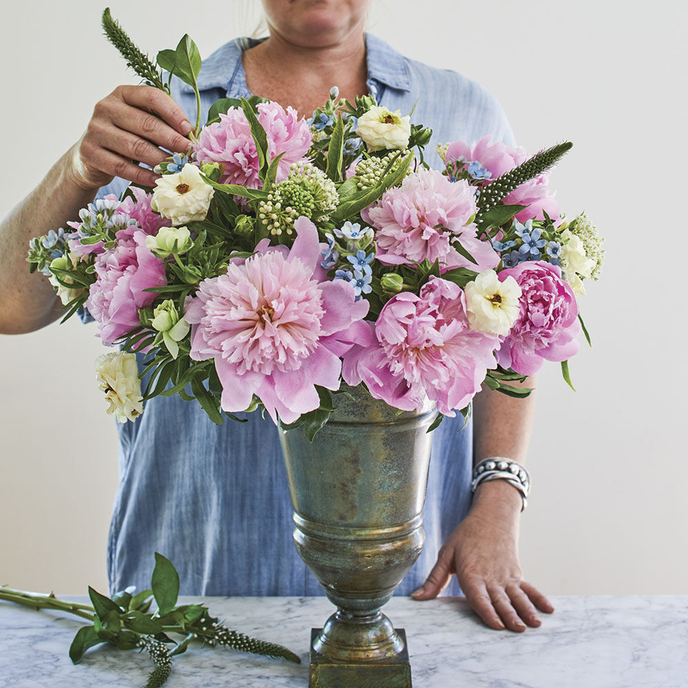 floral designer Kirk Whitfield places blooms of milkweed as the finishing touch to her vase of pink peonies, blue tweedia, and white butterfly ranunculus