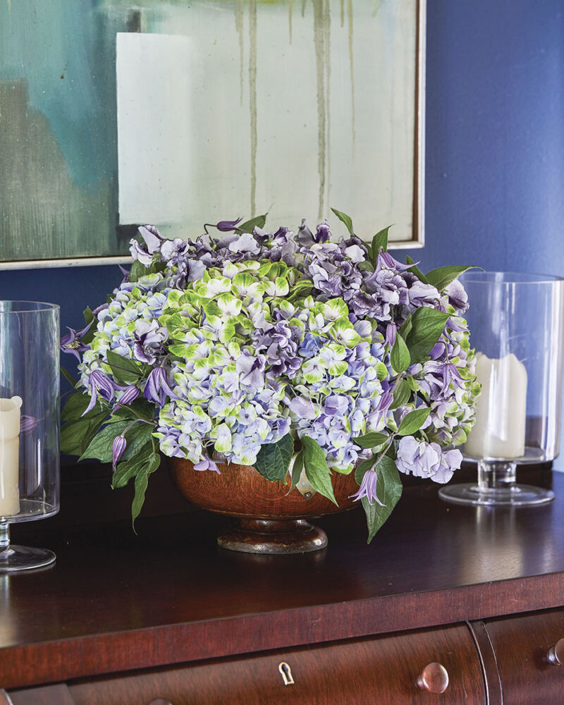 A purple floral arrangement by Kirk Whitfield of K & Co Flowers in a room painted royal blue. The arrangement, which includes sweet peas, hydrangea, and clematis, fills a large bowl set on a dark wood sideboard. An abstract painting, also featuring blue tones, hangs in the background