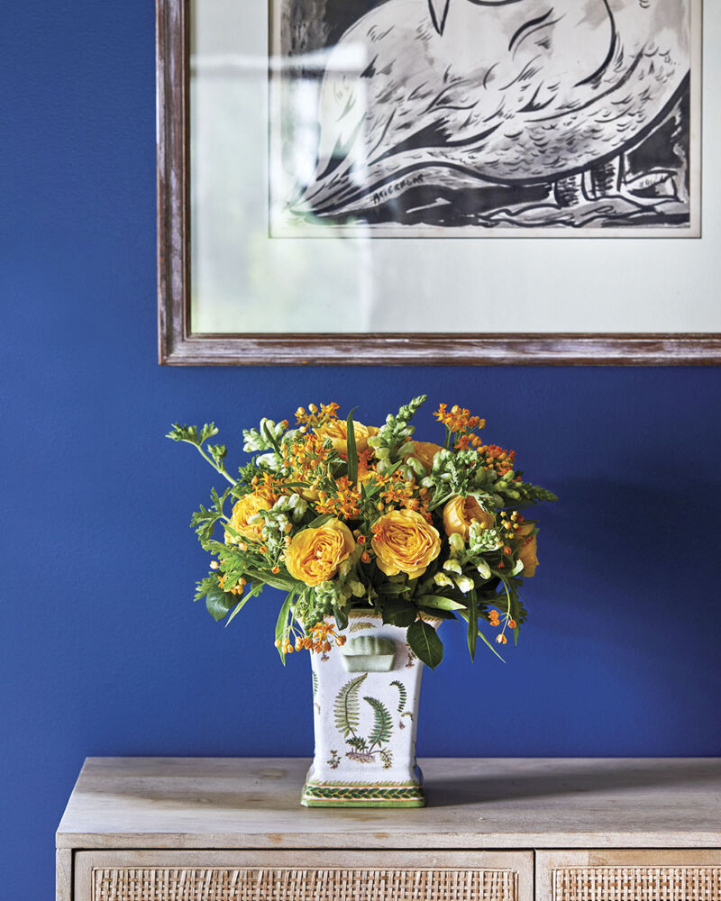 A vibrant yellow floral arrangement of dianthus, roses, snapdragons, scented geranium, and asclepia (milkweed) contrasts with the royal blue wall.