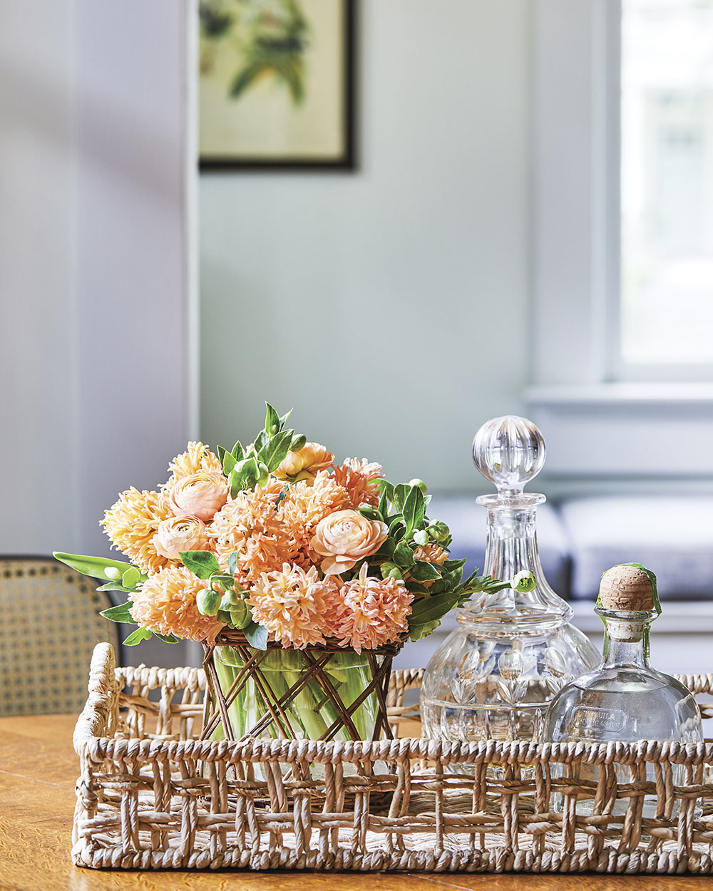 Floral designer Kirk Whitfield placed a peach-color floral arrangement, featuring hyacinth, ranunculus, and hellebores, in a woven tray beside a pair of crystal decanters. The room beyond, which boasts a tall window, is painted a soft pale green.