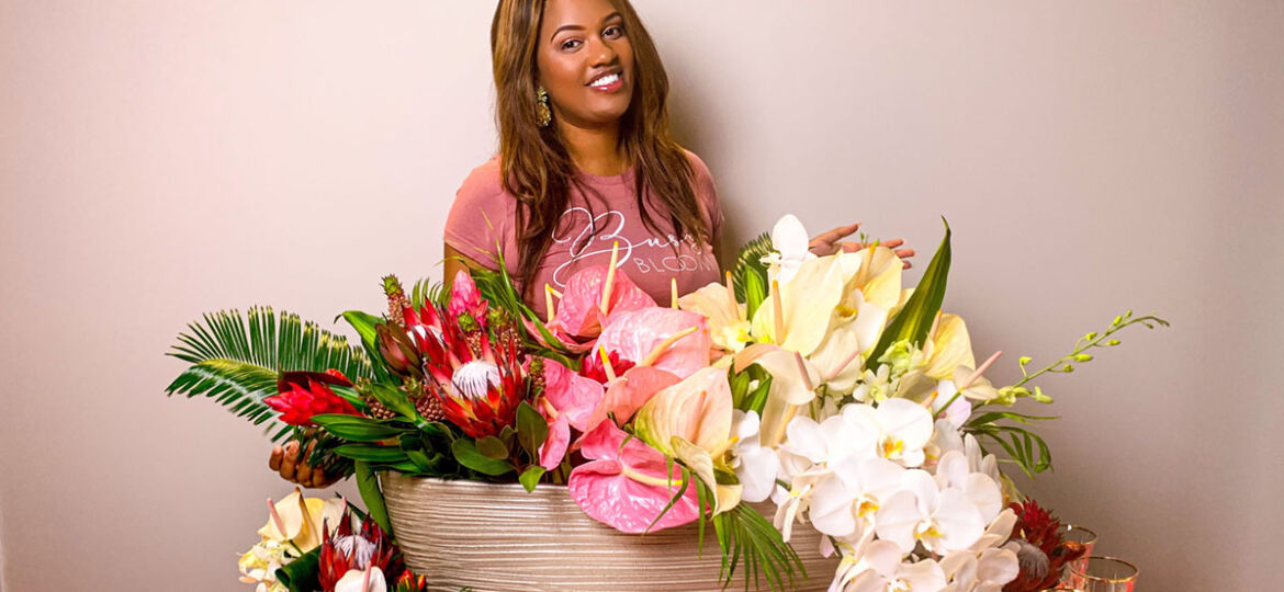 Leneille Moon, a black floral and event designer and owner of Special Event Factory in Atlanta, stands behind a large tropical ombre floral arrangement