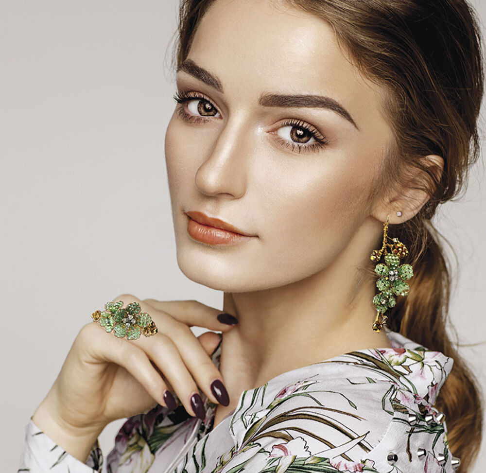 A model wearing a floral blouses poses with floral-inspired cocktail ring and earrings, both featuring green stones, by jewelry designer Mindy Lam