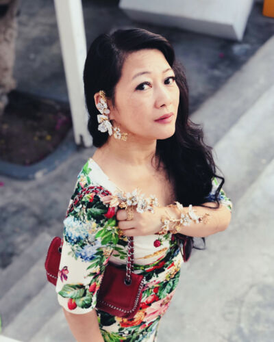 A portrait of jewelry designer Mindy Lam, a woman of asian descent with long wavy black hair, wearing a floral dress and her floral-inspired ring, bracelet cuff and earrings. She holds red clutch tucked under one arm.