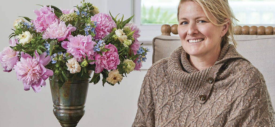 Portrait of floral designer Kirk Whitfield, wearing dark jeans and a tan cable knit shawl-style sweater, sitting next to a vase of pink peonies accented with smaller blue and white flowers