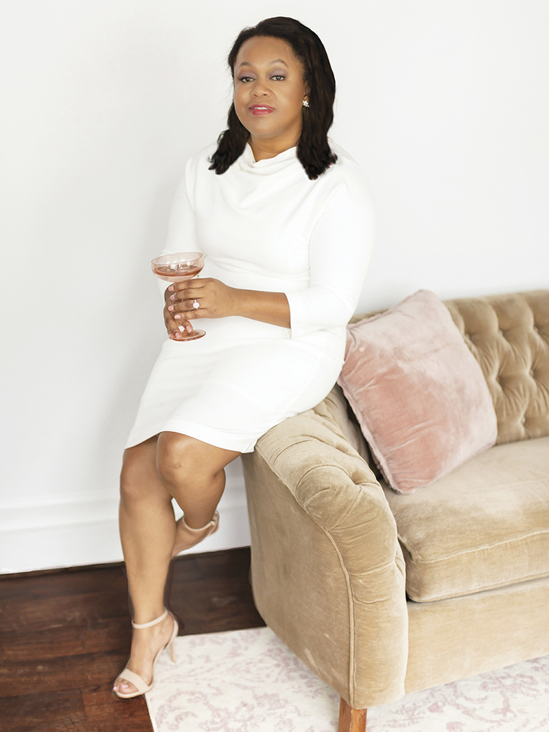 Stephanie Summerson Hall, the black entrepreneur behind Estelle Colored Glass, wears a white knee-length dress with ¾ sleeves, and leans against a tan tufted velvet sofa