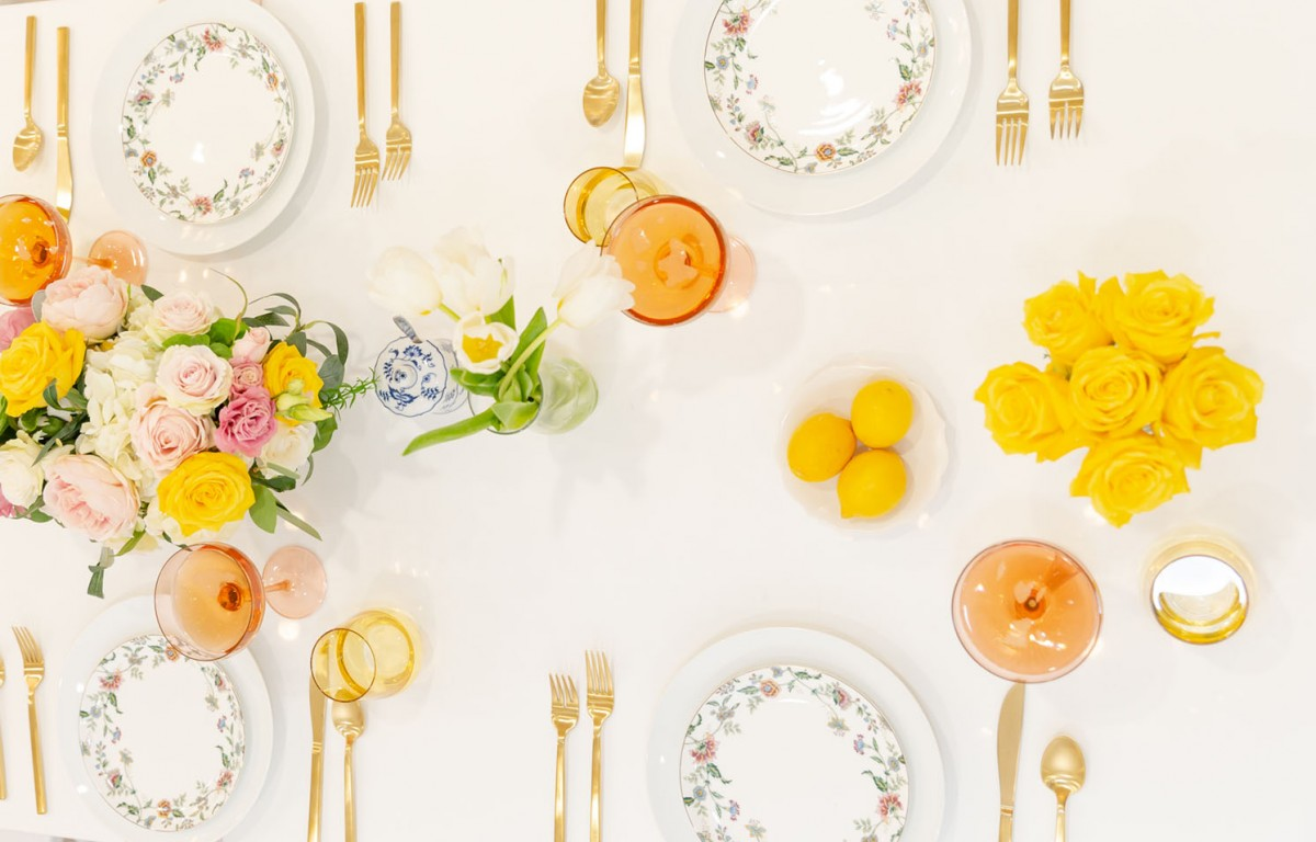 Table setting with peach handblown glass stemware and yellow tumblers from Estelle Colored Glass, gold-toned flatware, and white dinner plates rimmed in a floral pattern, all on a white table cloth. Bowls a lemons, a vase of bright yellow roses, a vase of white tulips, and a larger centerpiece of peach, pink and yellow garden roses and other blooms also decorate the table.