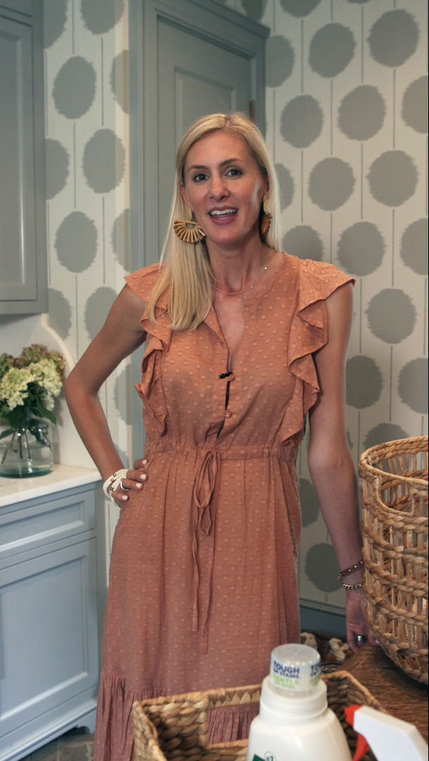 Interior designer Ashley Gilbreath stands in a stylish, functional laundry room she created for a client
