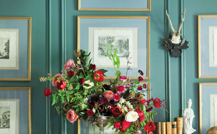 Floral design by Amy Osaba in an antique silver compote against a teal blue wall
