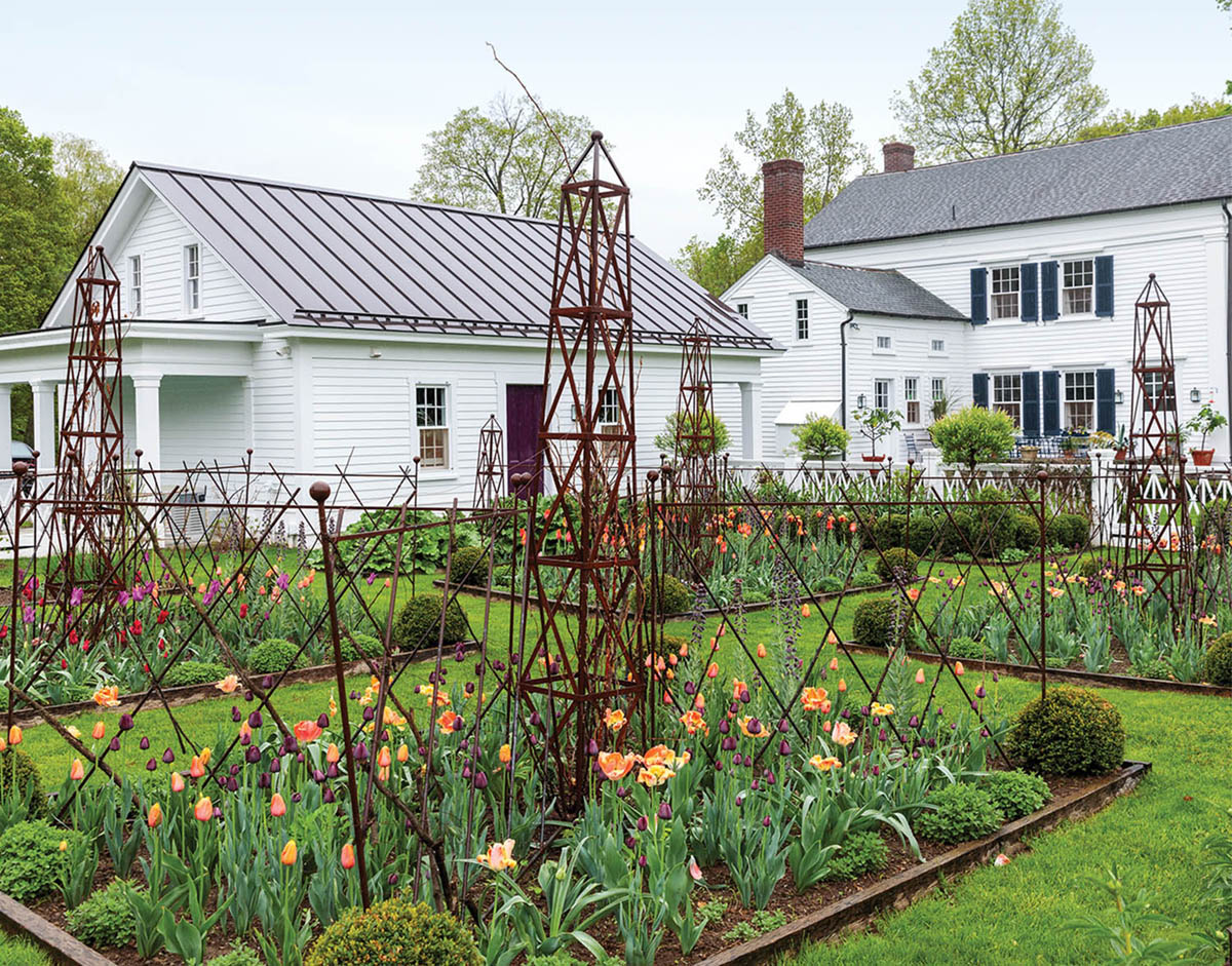 """White farmhouse and rustic garden parterres blooming with tulips at his Millbrook country home, from the pages of his book """"A Year at Clove Brook Farm"""" (Rizzoli)"""