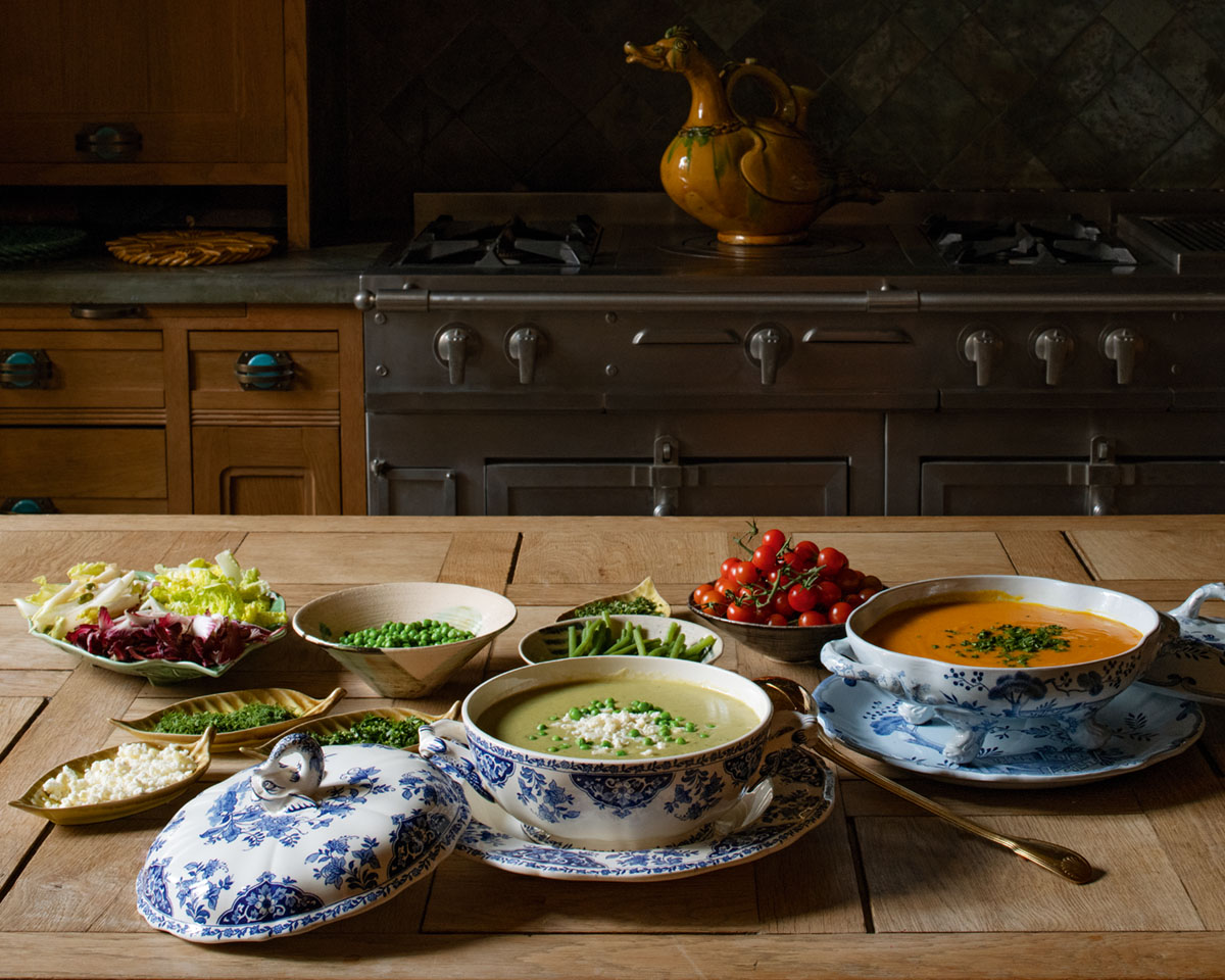 Terry De Gunzburg's recipe Pea, Zucchini, Lettuce, and Cucumber Soup served in a blue-and-white tureen, on a rustic wooden table by the kitchen stove. Also pictured: salad, grape tomatoes, green beans, small serving dishes of garnishes, and another soup.