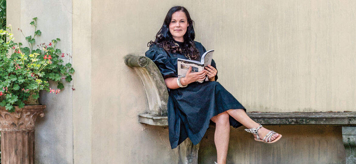 Betty Soldi, author of Inkspired (translated into eight languages), sits on a sandstone bench leaning against a wall decorated with classical flourishes.