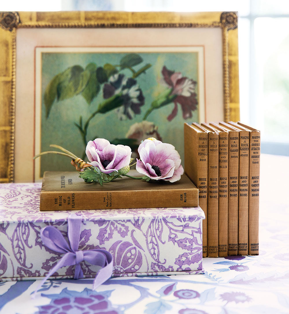 A vignette from the book Charlotte Moss Flowers including a framed floral painting, a set of vintage gardening books, two purple blooms, a present wrapped in a purple-on-white floral paper, all arranged on a purple-on-white floral print fabric
