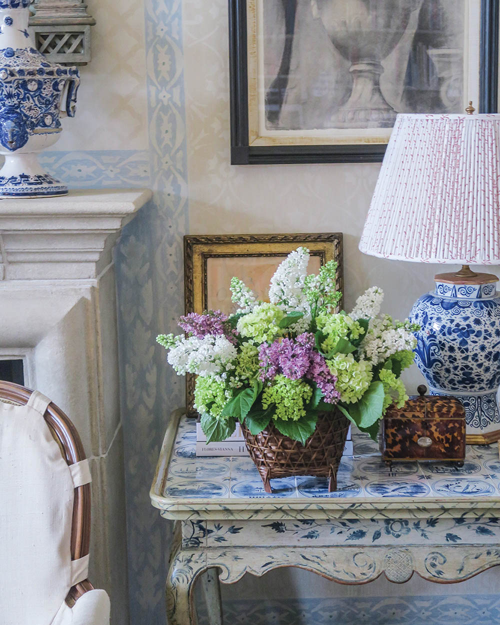 interiors vignette featuring a vase of lilacs on a side table beside a blue-and-white chinoiserie lamp