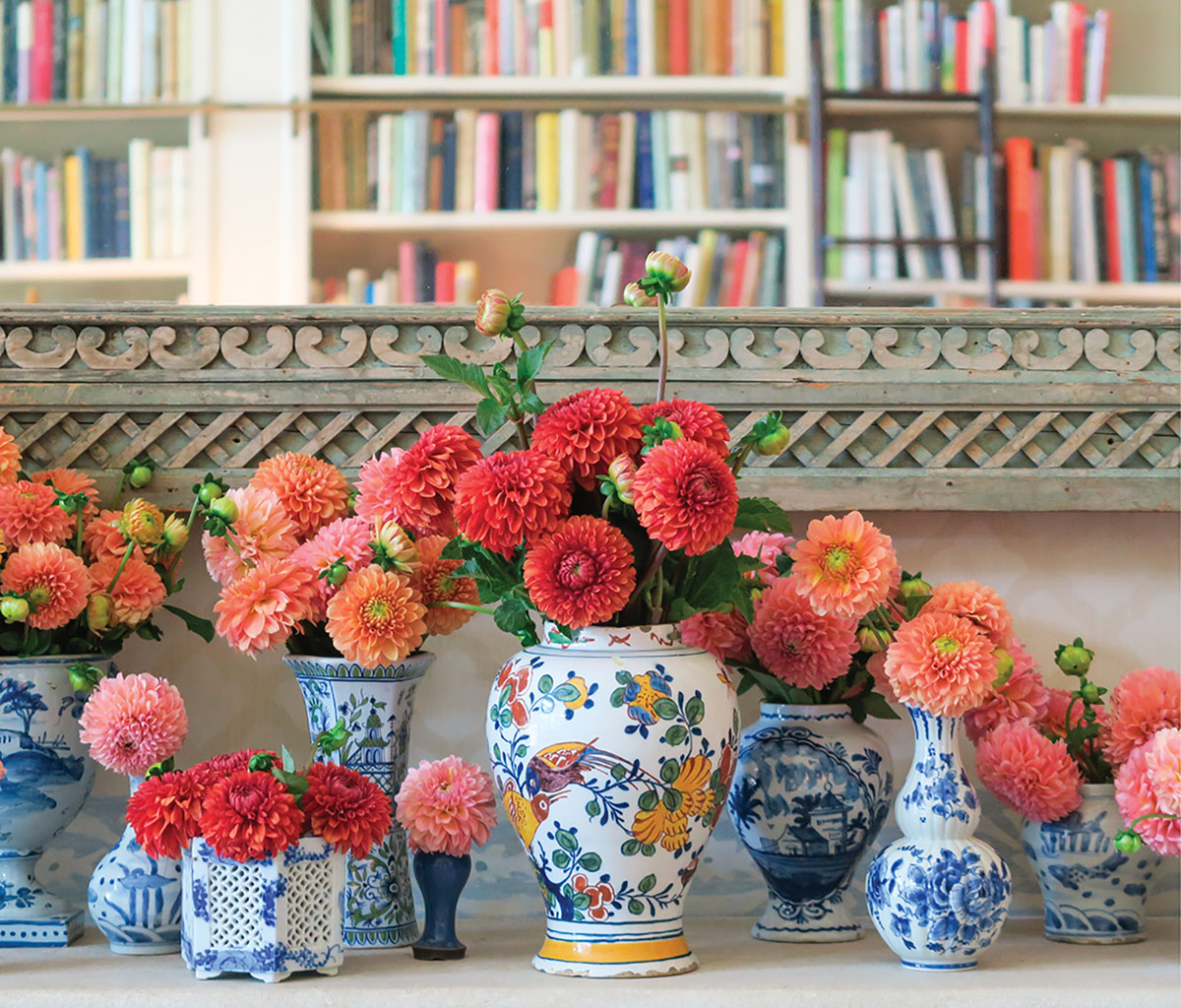 An assortment of blue-and-white chinoiserie vessels filled with dahlia blooms ranging from coral to red