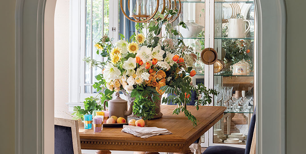 Framed by an arched entrance, a linear light fixture draws the eye through the dining room. The centerpiece features amaryllis, roses, 'Italian White' sunflowers, French tulips, wild grapevine, and wisteria. All floral designs by Jimmie Henslee. Interiors by Denise McGaha. Location: Dallas' historic Highland Park