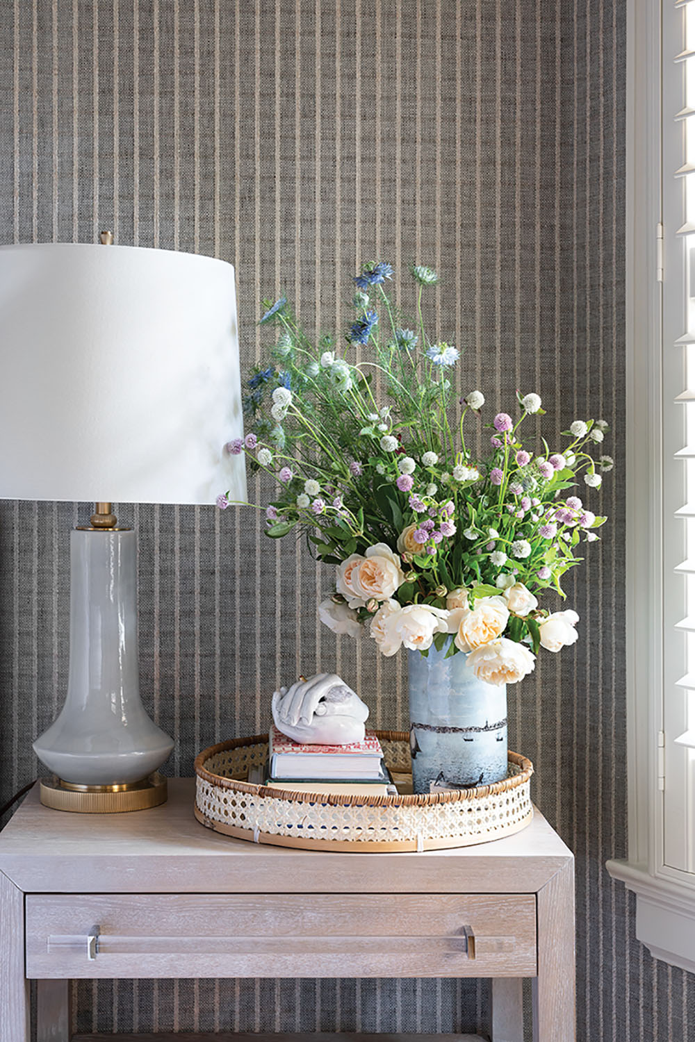pickled wood bedside with a lamp, tray, and floral arrangement
