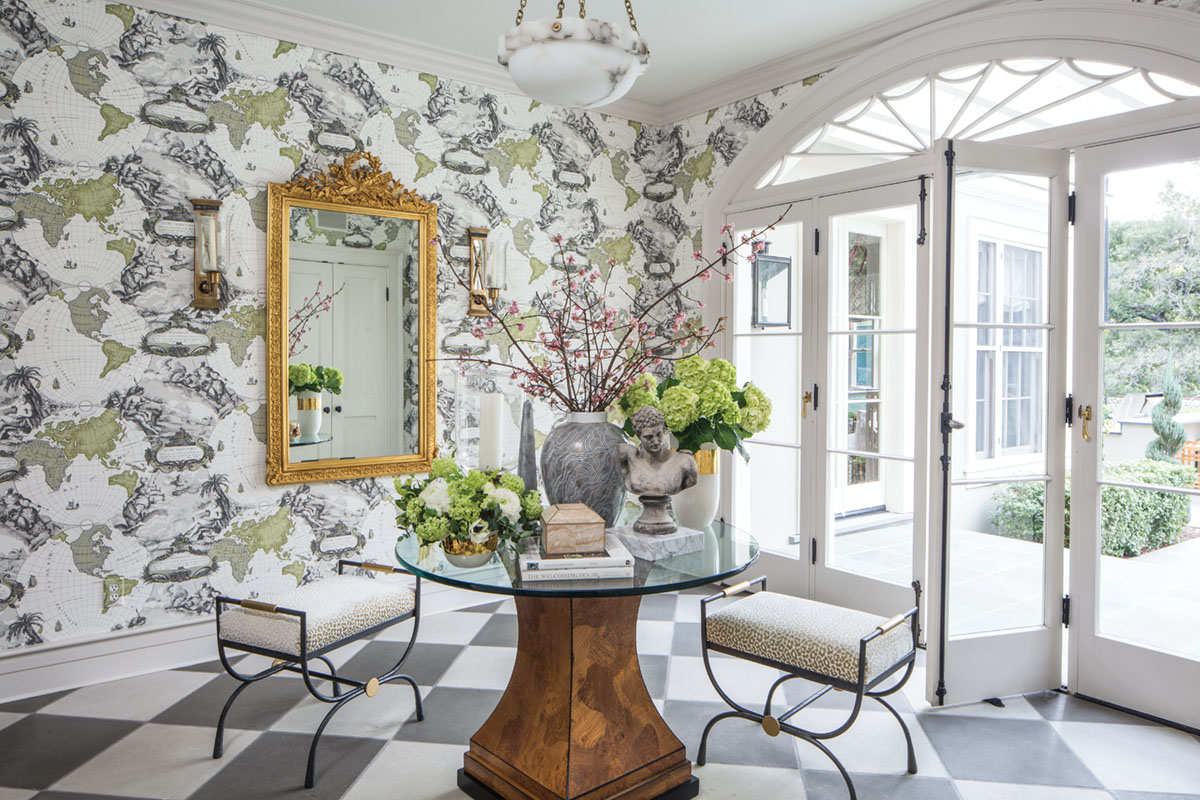 Emily Ruddo and her clients call this space the atrium because of the generous natural light. Pink quince and green viburnum complement the Pierre Frey wallpaper.