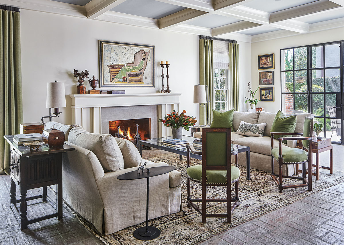 living room featuring a grid of exposed rafters, a fireplace, soft white walls, and a mix of neutral and sage green textiles