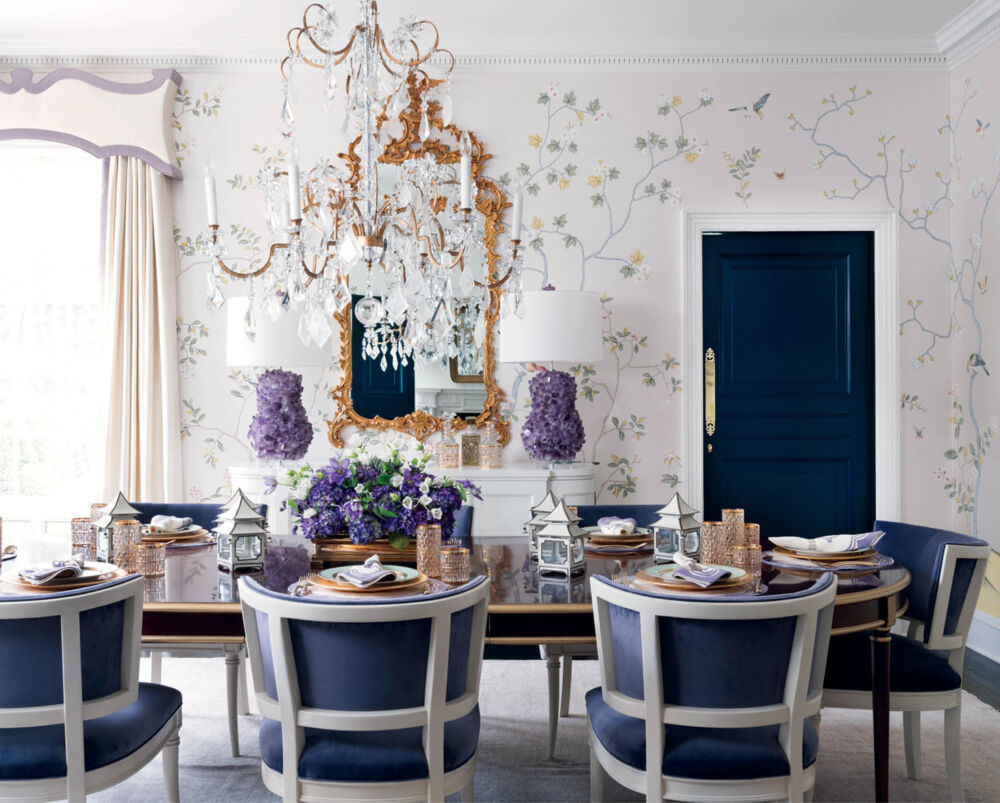 A dining room by interior designer Melanie Turner, featured in her book, Inviting Interiors. The room features a light and airy floral wallpaper on a white background, dental molding, a grand crystal chandelier, a gilt mirror flanked by two lamps with amethyst bases. She mixes wood tones, with a dark wood dining table with gild edges pared with white-wood framed dining chairs with navy upholstery. The door is painted navy.