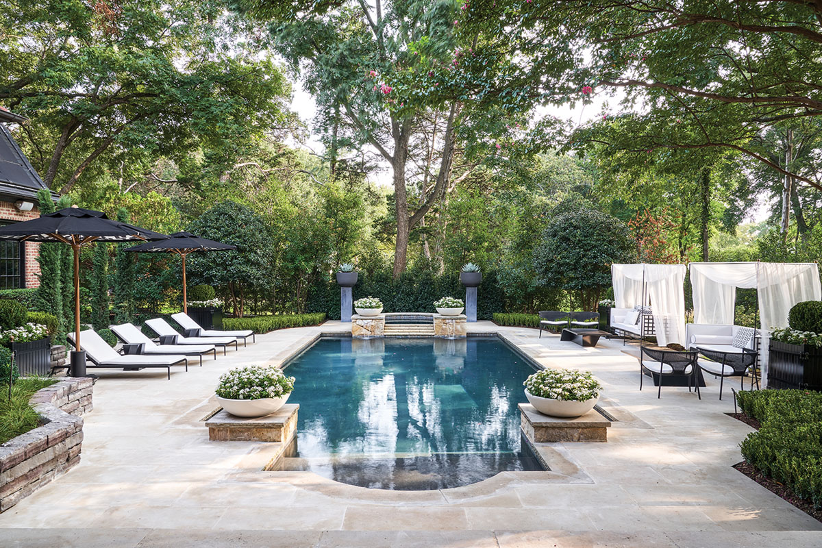 elegant pool and patio area furnished with outdoor seating and potted plants