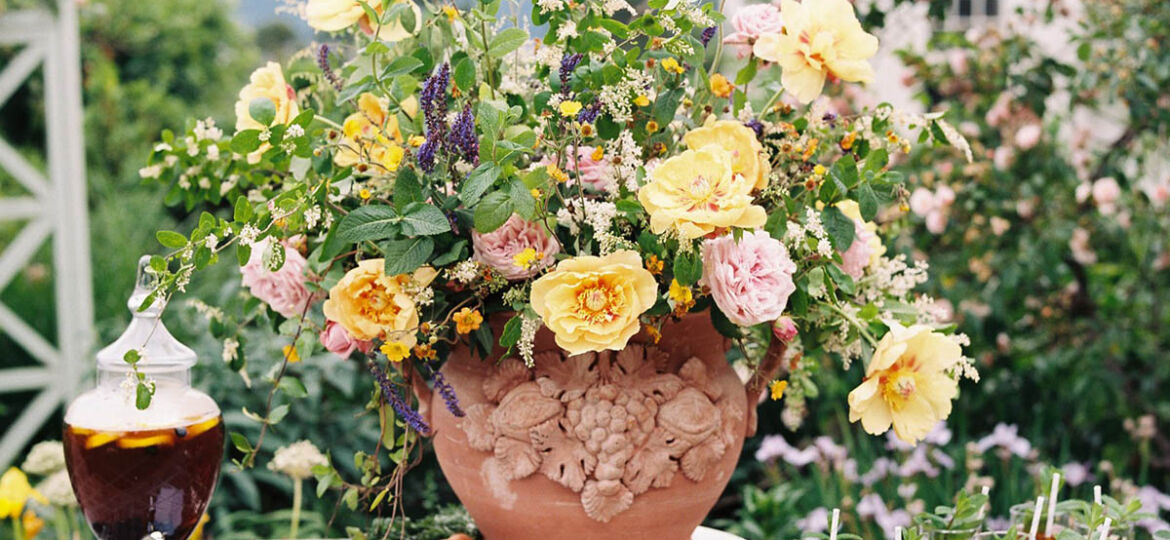 A large yellow, pink, and green floral arrangement at the center of a table filled with glasses of sweet tea, table set in the rose garden at Moss Mountain Farm, created by The Velvet Boxwood for duck, duck, goose-themed children's social