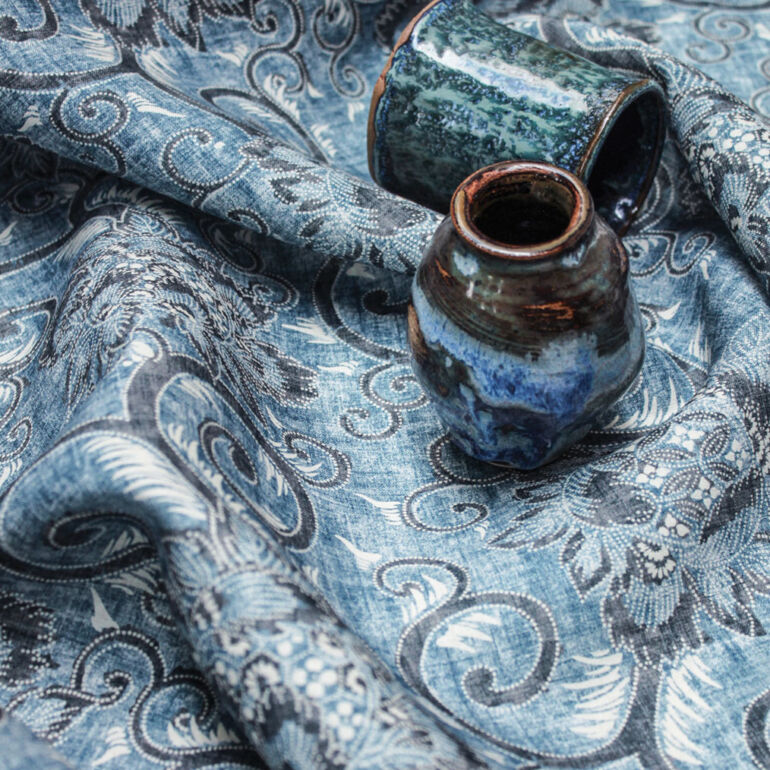 Indigo blue fabric designed by Suzanne Tucker, pictured with blue pottery pieces