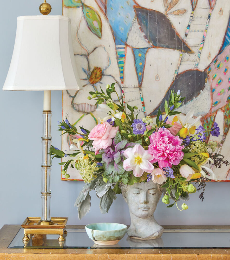 Floral design by The French Potager featuring spring flowers in a concrete cast bust