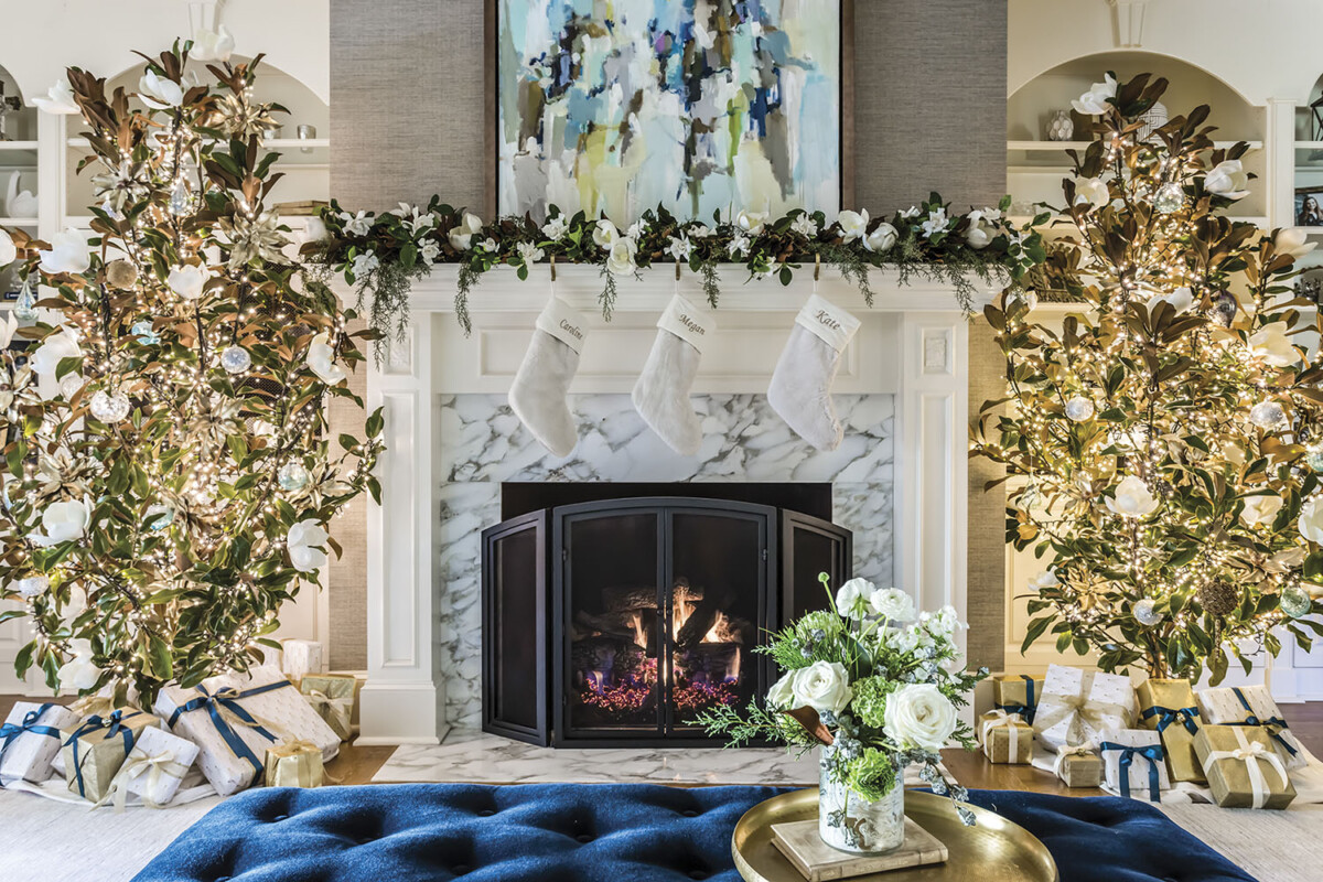 A pair of magnolia Christmas trees flank a mantel decorated with a garland and white stockings for the holidays in a Raleigh, NC, home decorated by Vicky Serany