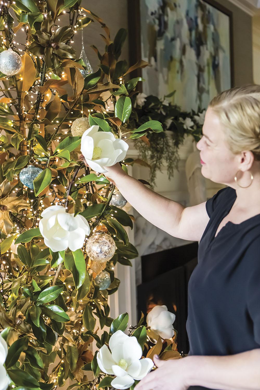 Erin Weston of Weston Farms adds faux magnolia blooms to a fresh magnolia tree