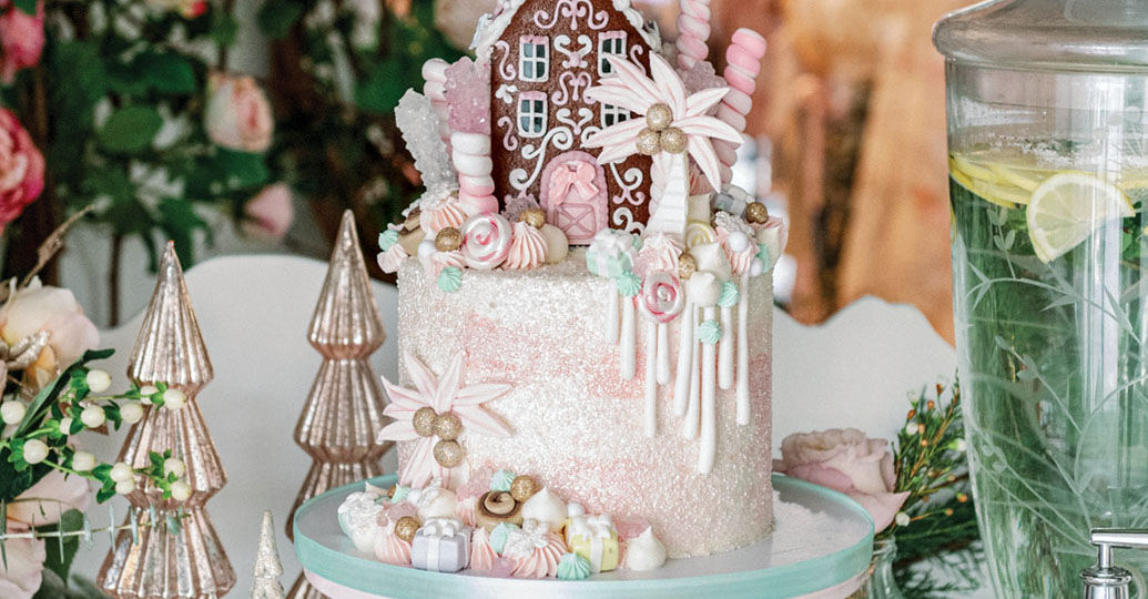 fanciful gingerbread house-topped cake on a pedestal at the Palm Beach Lately and LoveShackFancy holiday party