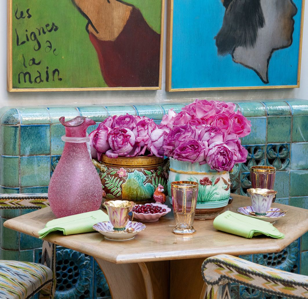 A table setting beside a blue and green tiled wall at the Parisian home of Terry de Gunzburg. Garden roses tinged bright pink fill a pair of colorful porcelain vessels bearing floral motifs. The setting also features artful glassware (pitcher, drinking glasses), china teacups, and a serving dish of pomegranate seeds, all carrying through the pink color scheme. Pale green napkins contrast with the pink and tie into the blue and green featured in the tile wall, artwork, and chair upholstery