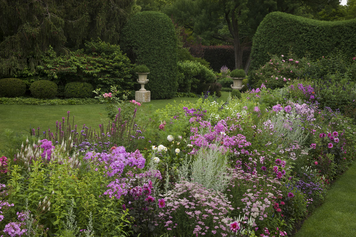An English-garden style parterre featuring blooming perennial beds and expanses of green lawn surrounded by precisely groomed, curving walls of tall hedges. Camp Rosemary in Lake Forest)