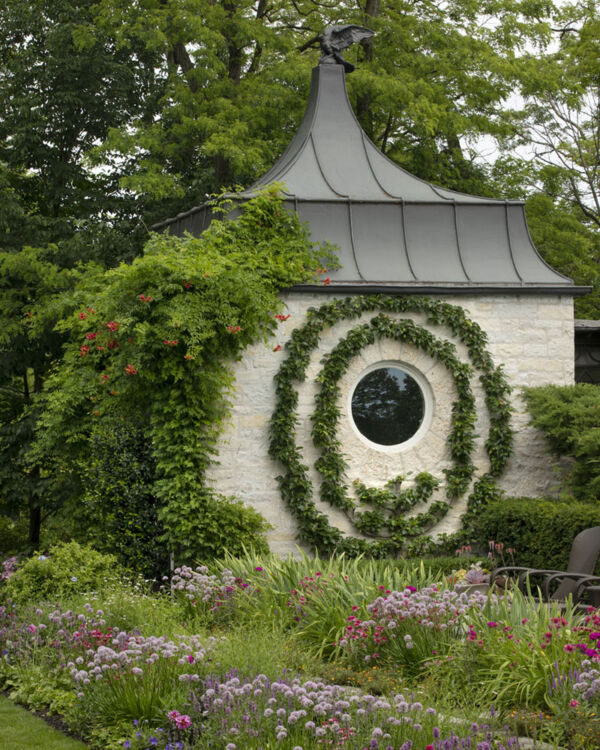 """Caption from the book Gardens of the North Shore of Chicago: """"A vigorous trumpet vine and pear espalier encircles a poolhouse window. The two-tiered perennial border features betony, coneflower, phlox, summer allium, iris and plumbago."""" (Edgecliff in Winnetka)"""