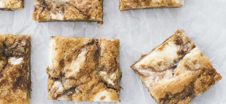 Squares of Cinnamon Roll Blondies an parchment paper