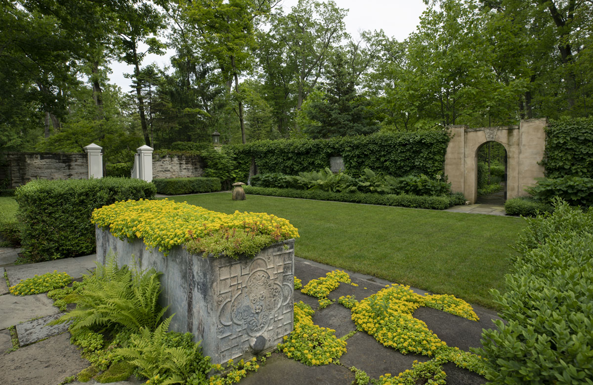 """Caption from the book Gardens of the North Shore of Chicago: """"The centerpiece of the walled garden is a large lead cistern overflowing with sedum facing a lawn panel. Surrounding borders are filled with ferns, epimedium, ligularia, and hydrangeas climbing the stone walls."""" (Crab Tree Farm in Lake Bluff)"""