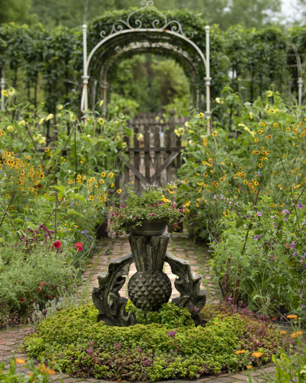 """Caption from the book Gardens of the North Shore of Chicago: """"An eighteenth-century Scottish thistle finial sits in a bed of sedums in a cutting garden of heirloom annuals and herbs. An antique wrought-iron arbor, found in an Oxford University courtyard, connects to a second cutting garden."""" (Kelton House Farm in Fredonia, Wisconsin)"""