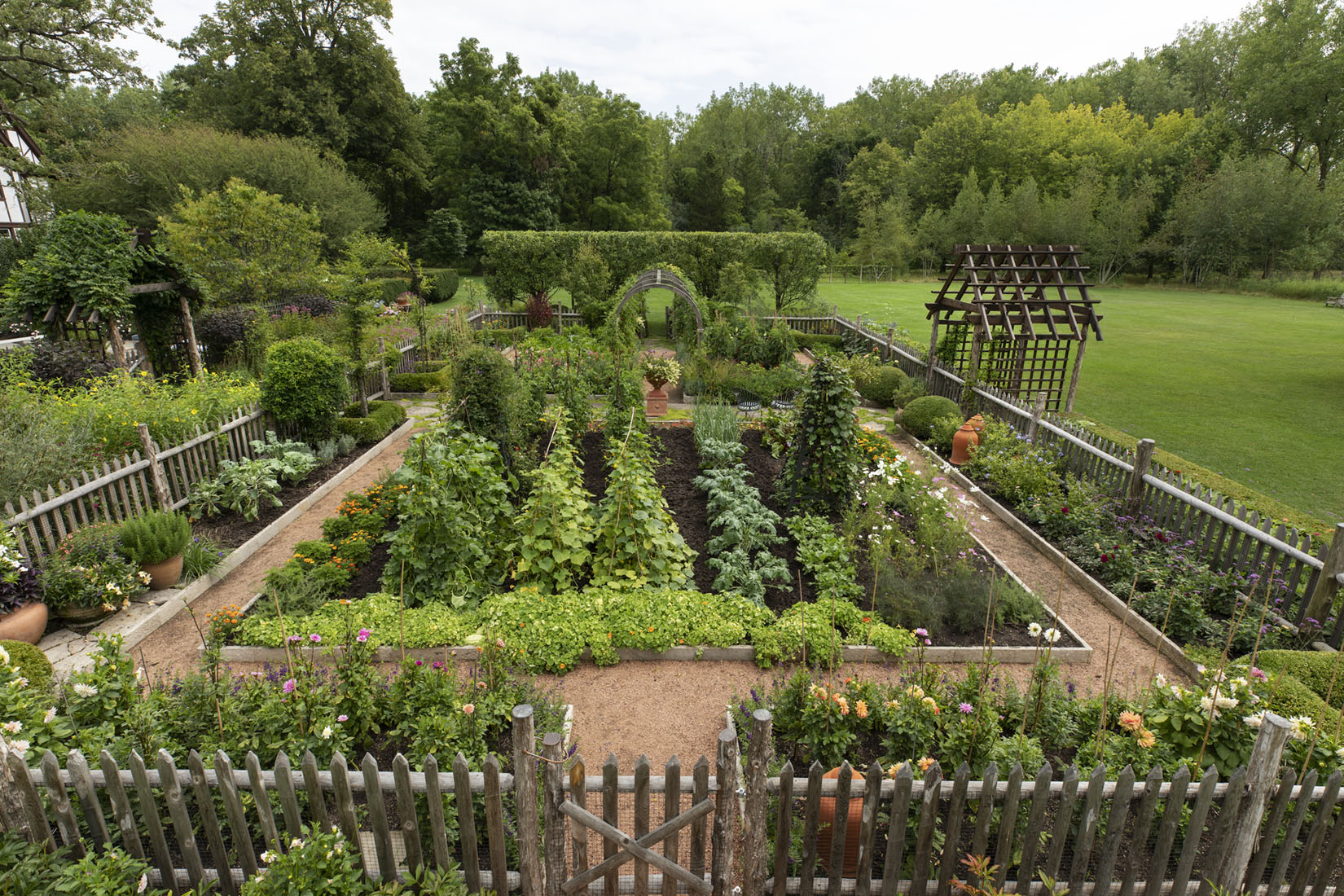 """Caption from the book Gardens of the North Shore of Chicago: """"Squash, beans, tomatoes, and herbs mix with nasturtiums, cosmos, and dahlias in the vegetable garden."""" (Old Mill Farm in Lake Forest)"""