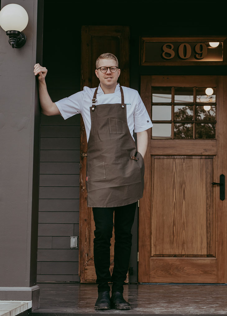 portrait of of chef Hunter Jackson, wearing an apron, white shirt, and black pants, standing on the front porch of his restaurant Elvie's in Jackson, MS