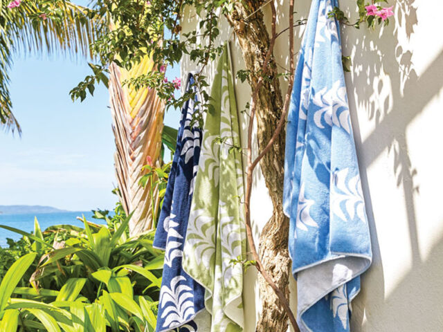 Beach scene with 3 towels in assorted colors from Heather Chadduck Hillegas' collection for Weezie hung on a white stucco wal