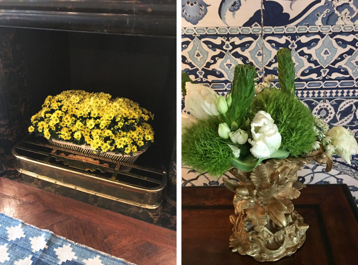 (left) a basket of potted yellow mums fills a fireplace. (right) a simple green and white floral arrangement in an antique brass vase with intricate botanical details