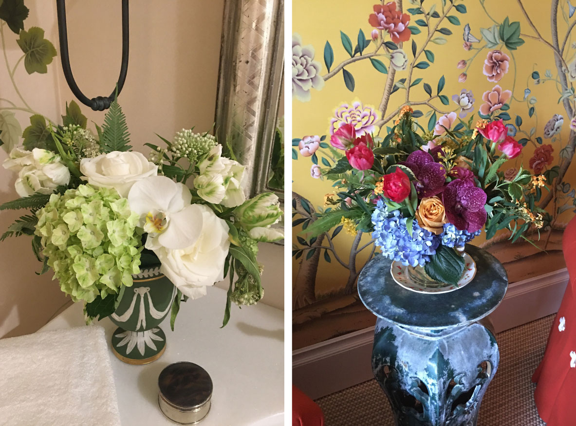 (left) green and white floral floral arrangement by the bathroom sink. (right) colorful floral arrangement with blue hydrangeas, purple orchids, hot pink tulips, and coffee colored roses, mirroring the wallpaper behind it